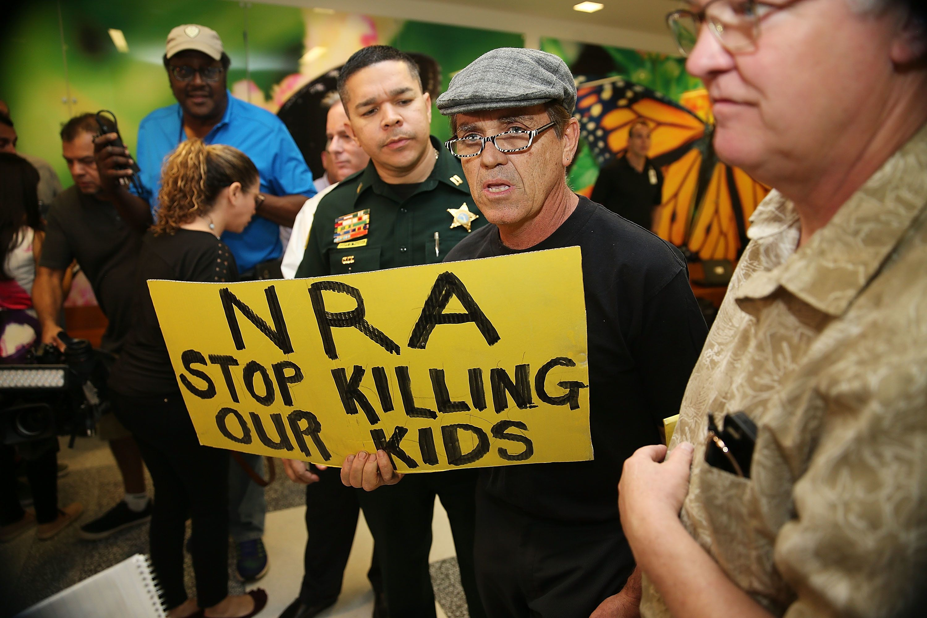 FORT LAUDERDALE, FL - FEBRUARY 15: A protester holds a sign that reads, 'NRA Stop Killing Our Kids', outside the court-room where Nikolas Cruz, 19, a former student at Marjory Stoneman Douglas High School in Parkland, Florida, was having a bond hearing in front of Broward Judge Kim Mollica at the Broward County Courthouse on February 15, 2018 in Fort Lauderdale, Florida. Mr. Cruz is possibly facing 17 counts of premeditated murder in the school shooting.  (Photo by Charles Trainor Jr. - Pool/Getty Images)