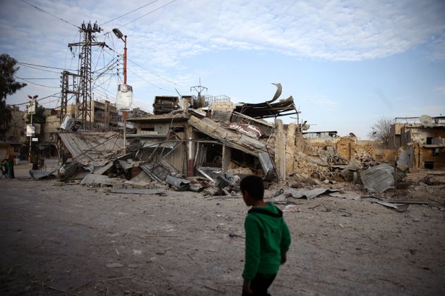 A child walks near damaged buildings in the besieged town of Douma, Syria, on Feb. 20,