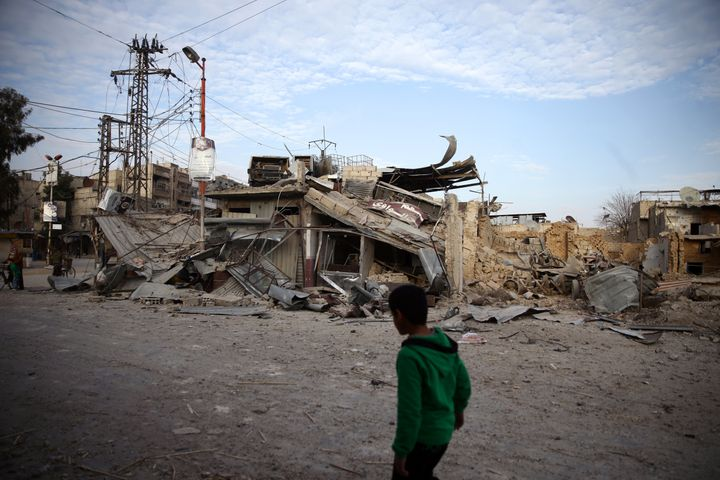 A child walks near damaged buildings in the besieged town of Douma, Syria, on Feb. 20, 2018.