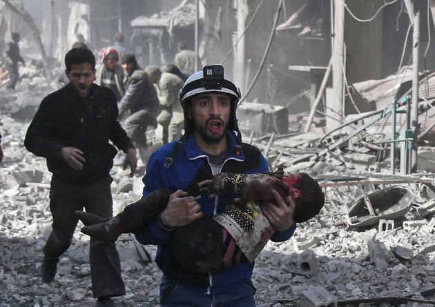 A Syrian civil defense member carries an injured child after a government bombing in the rebel-held...