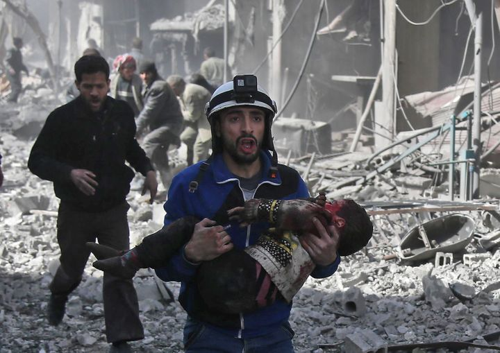 A Syrian civil defense member carries an injured childafter agovernment bombing in the rebel-held town of Hamouri