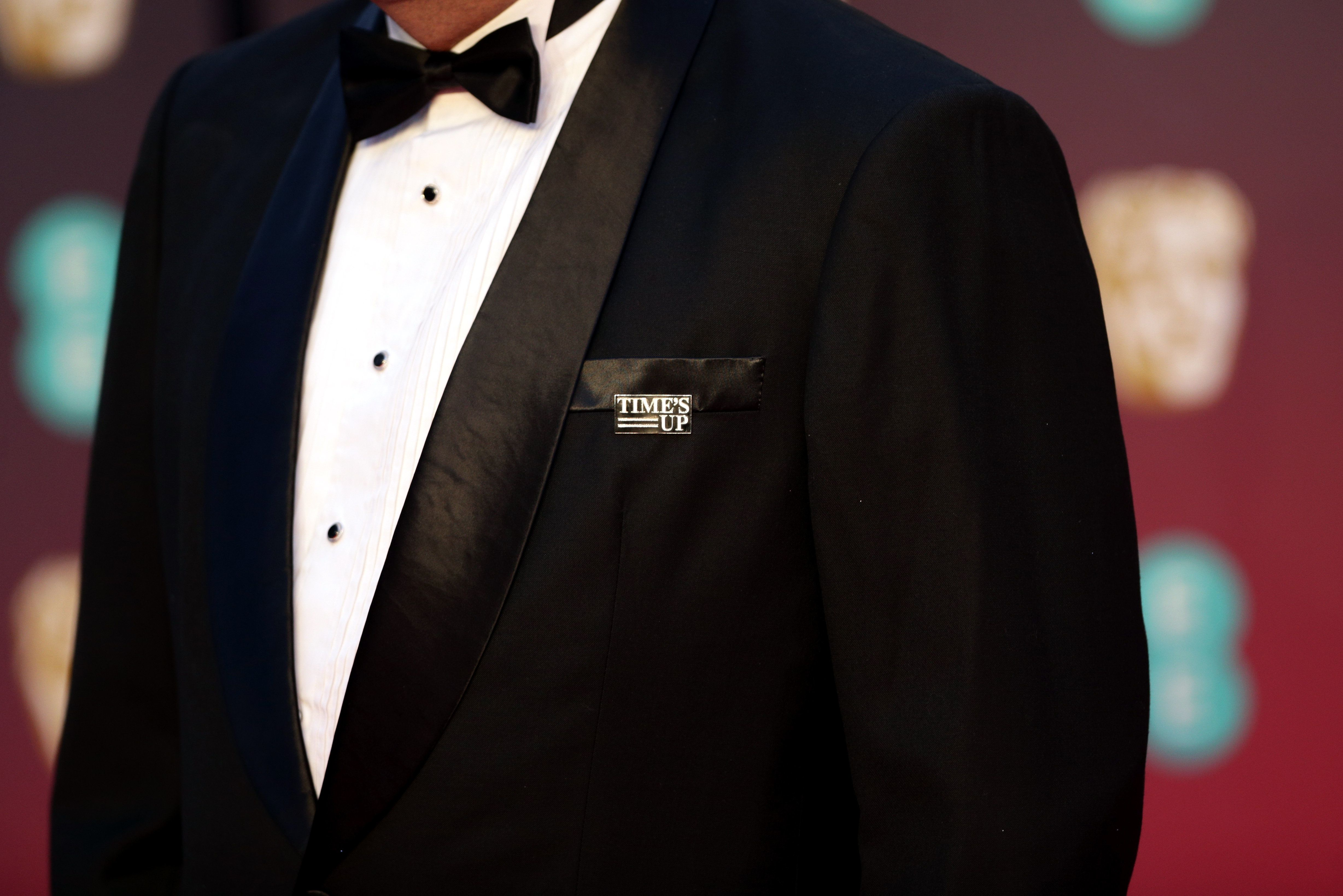 A guest on the BAFTA's red carpet wears a Time's Up pin in support of the anti-sexual misconduct