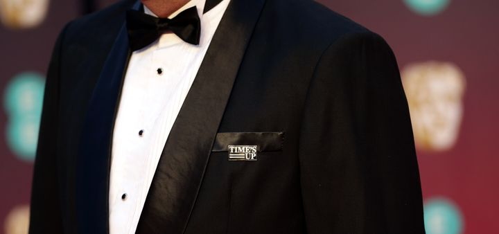 A guest on the BAFTA's red carpet wears a Time's Up pin in support of the anti-sexual misconduct initiative.