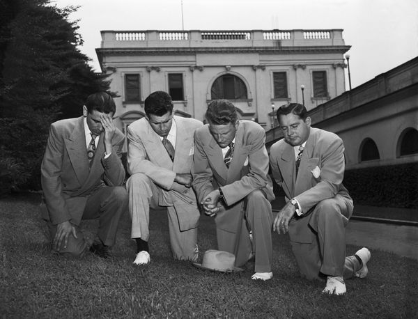 Kneeling in prayer on the White House lawn after their meeting with President Harry Truman are left to right: Jerry Beaver; C