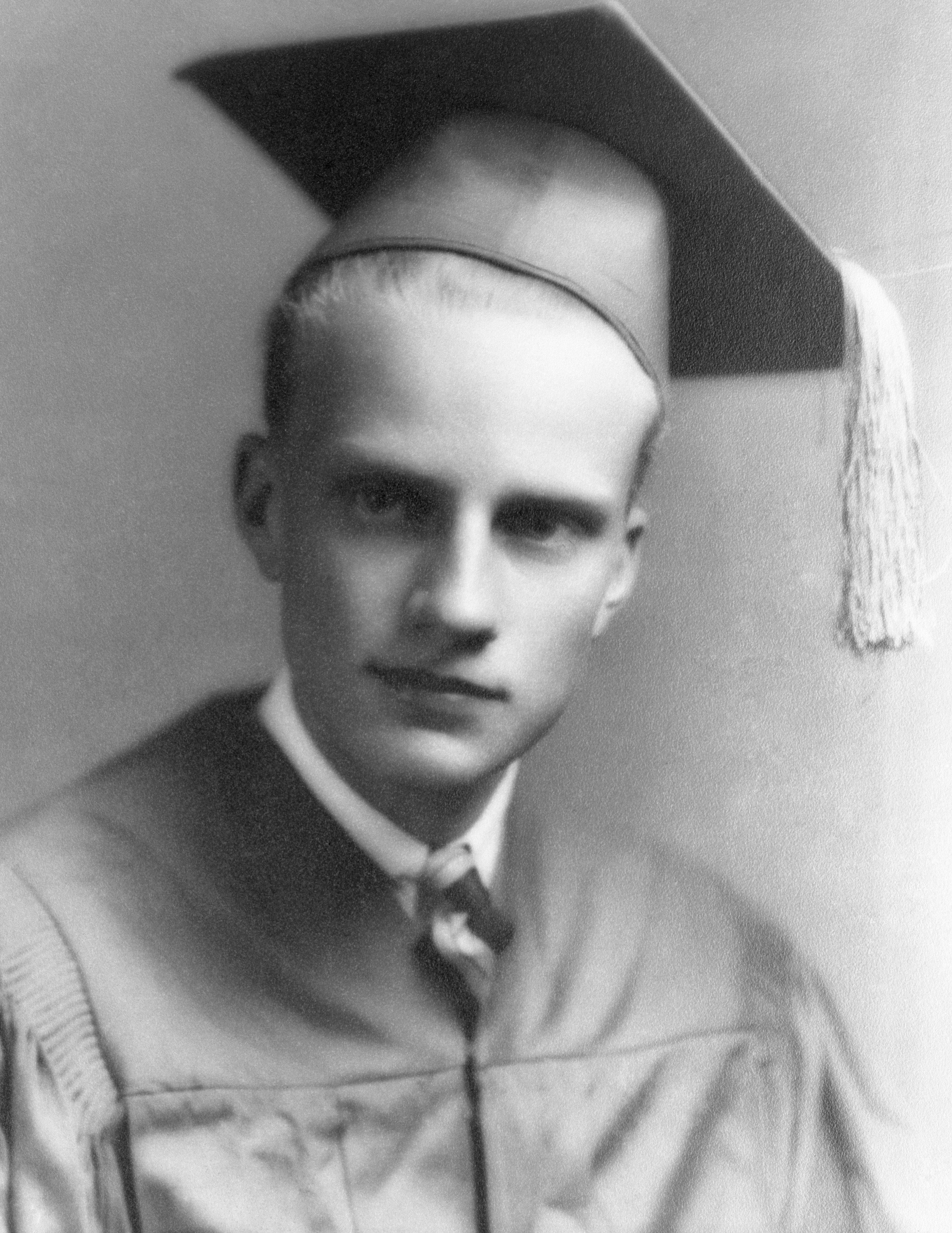 Evangilist Billy Graham cap and gown at age 17 on his graduation from Charlotte High School. Shortly before this date Billy had embraced religion at a local revival meeting and had decided on a career of the pulpit rather than that of a diamond.