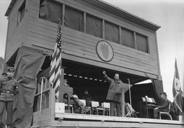 Graham raises his fist as he speaks to members of the 24th Infantry Division in Korea in February 1956.