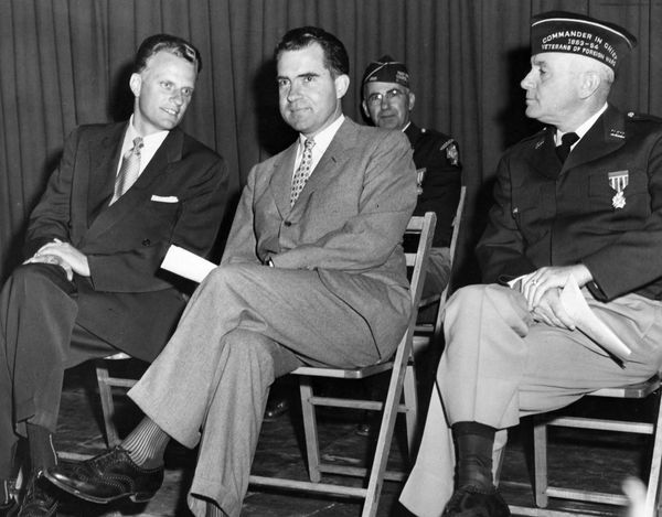 Then-Vice President Richard Nixon sits with Graham, left, and National Commander Merton B. Rice, at a memorial service during