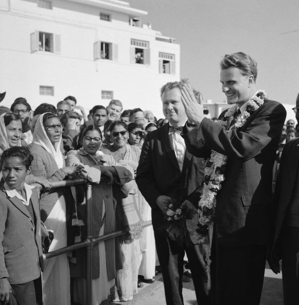 Graham, wearing a garland presented to him by welcomers in New Delhi, raises his hands in Indian greetings to crowds on hand