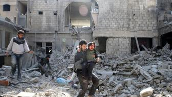 ATTENTION EDITORS - VISUAL COVERAGE OF SCENES OF INJURY OR DEATH A man carries an injured boy as he walks on rubble of damaged buildings in the rebel held besieged town of Hamouriyeh, eastern Ghouta, near Damascus, Syria, February 21, 2018. REUTERS/Bassam Khabieh TEMPLATE OUT
