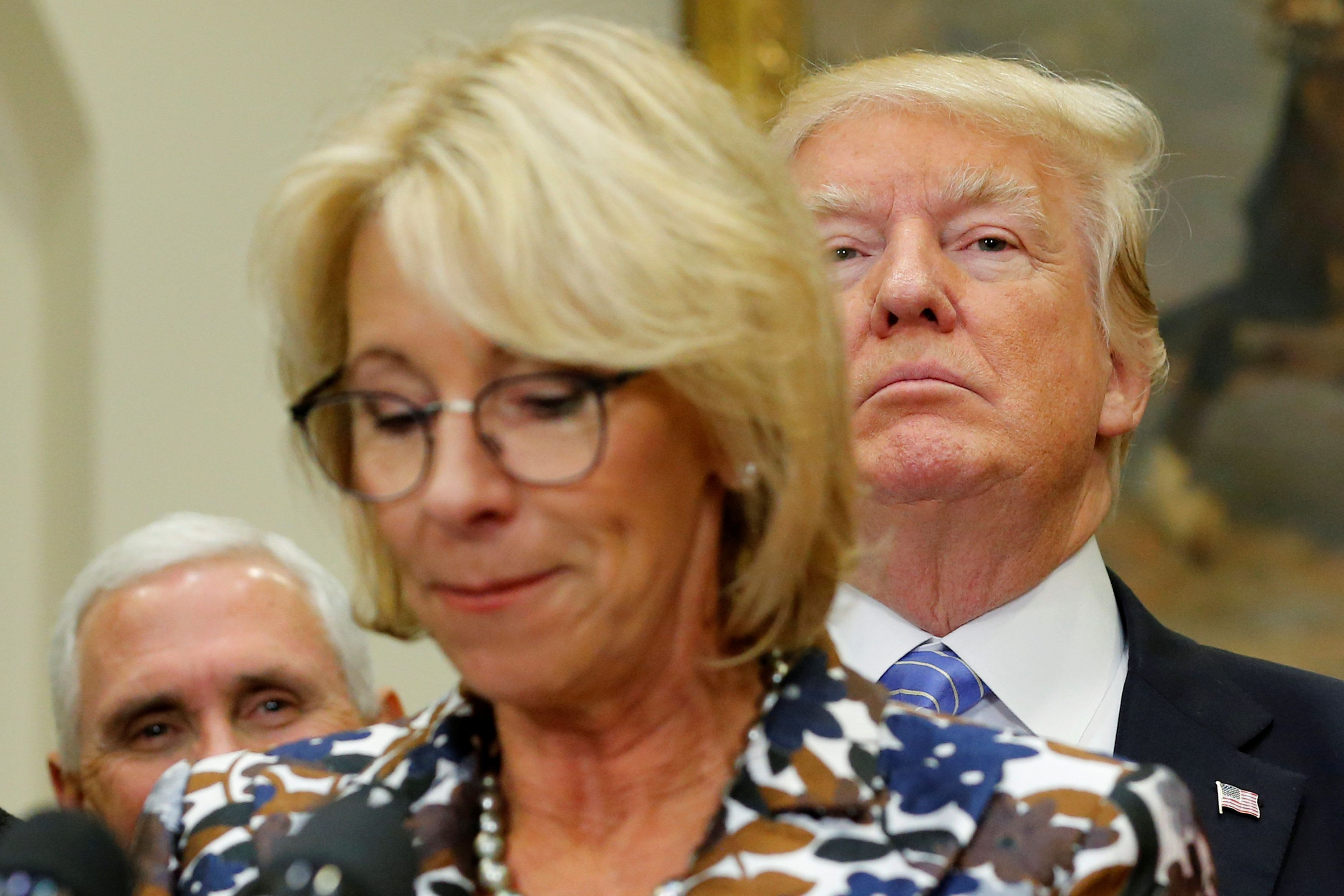 U.S. President Donald Trump (R, background) and Vice President Mike Pence (L) wait to interrupt Education Secretary Betsy DeVos as she speaks to students at a school choice event at the White House in Washington, U.S. May 3, 2017.  REUTERS/Jonathan Ernst