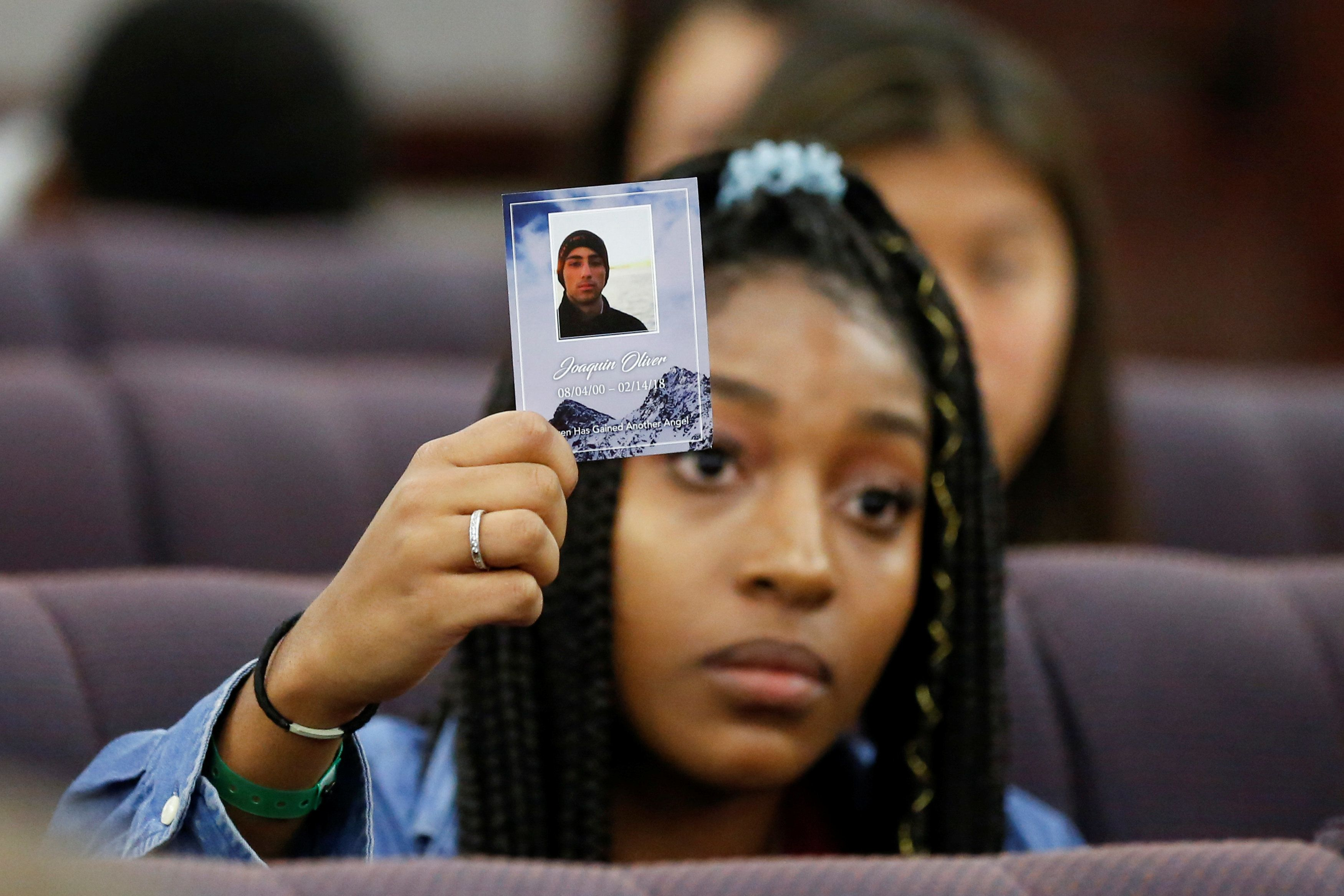 Tyra Hemans, a senior from Marjory Stoneman Douglas High School, holds a photo of her friend Joaquin Oliver, who died during