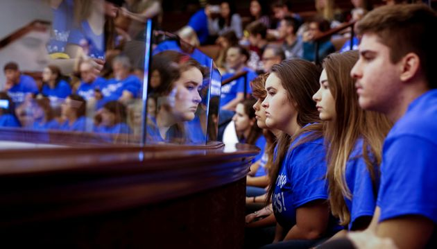 Students from Marjory Stoneman Douglas High School, wearing blue T-shirts, look on from the gallery above...