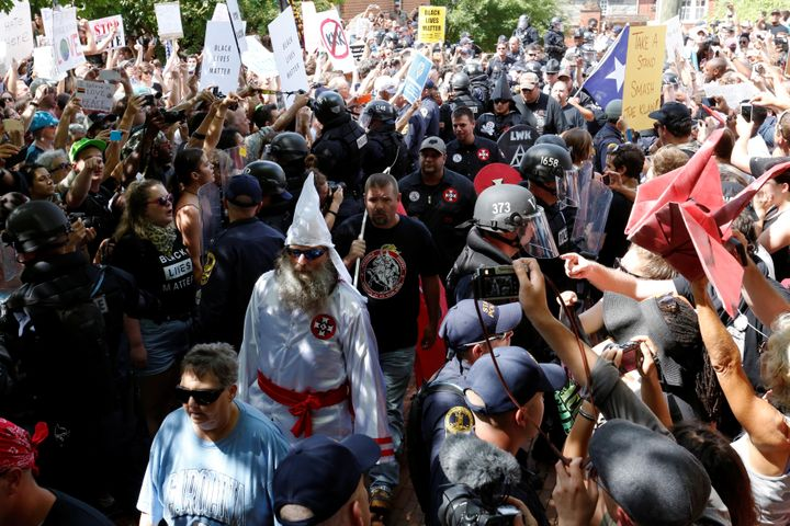Riot police protect members of the Ku Klux Klan from counter-protesters as they arrive to rally in opposition to city proposa