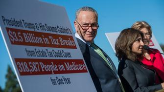 UNITED STATES - OCTOBER 18: From left, Senate Minority Leader Charles Schumer, D-N.Y., Neera Tanden, CEO of the Center for American Progress (CAP), and Sen. Elizabeth Warren, D-Mass., conduct a news conference on the east lawn of the Capitol on a CAP Action report saying that wealthy Americans, such as President Trump and his cabinet, would benefit from the GOP tax and budget proposals at the expense of the middle class on October 18, 2017. (Photo By Tom Williams/CQ Roll Call)