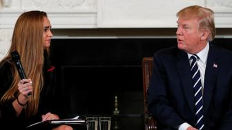 U.S. President Donald Trump, seated with Marjory Stoneman Douglas High School shooting surviving student Julia Cordover, hosts a listening session with Marjory Stoneman Douglas High School shooting survivors and students at the White House in Washington, U.S., February 21, 2018. REUTERS/Jonathan Ernst
