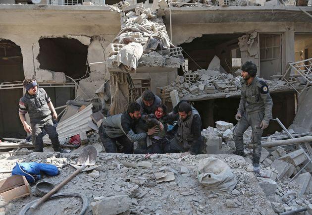 Unos hombres rescatan a una niña de los escombros entre las casas derruidas de Guta del