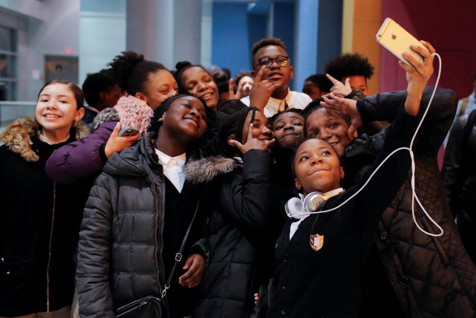 "A group of children takes a selfie as they arrive on the opening night of the film ""Black Panther"" at the AMC Magic Johnson H"