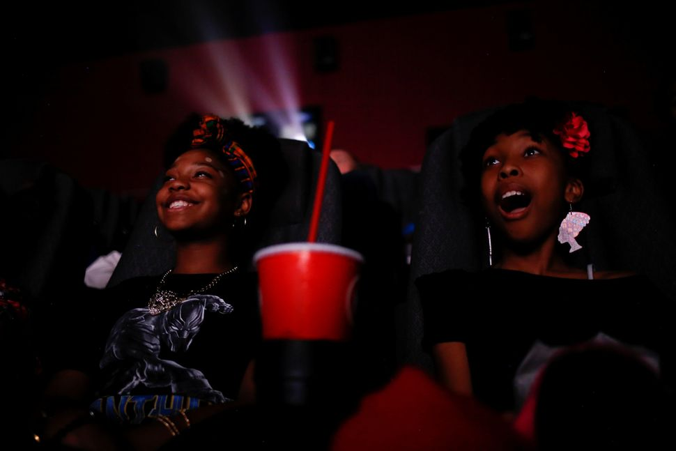 Sixth-graders Destiny Cox, left, and Allana Walker watch the film.