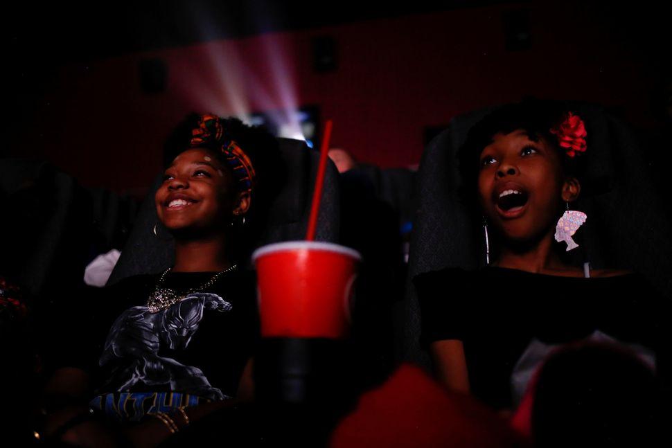 Sixth-graders Destiny Cox, left, and Allana Walker watch the film.
