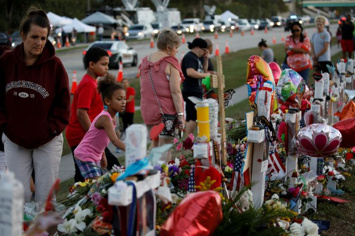 People grieve in front of crosses and Stars of David placed in front of the fence of the Marjory Stoneman Douglas High School