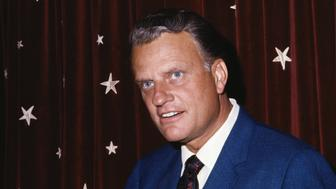 (Original Caption) Close-up photo shows evangelist Billy Graham in front of an American flag.