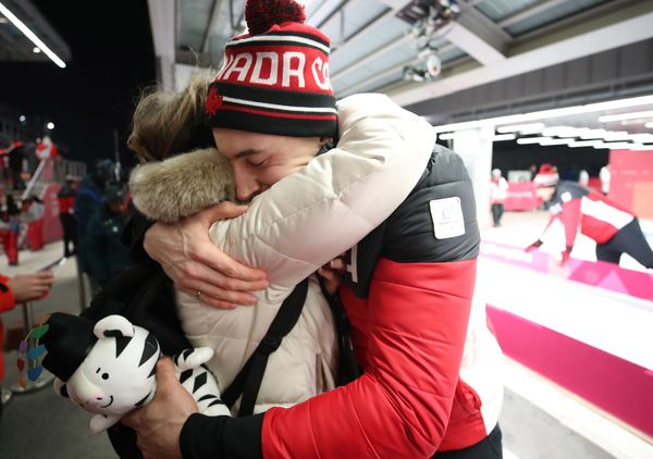 Janet Kopacz hugs her son Alexander Kopacz after he and Justin Kripps tie for the gold medal with a German sled in the two-ma