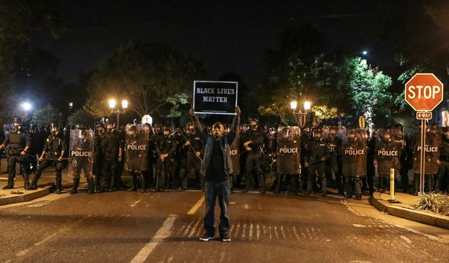A Black Lives Matter protester stands in front of St. Louis Police Department officers equipped with...