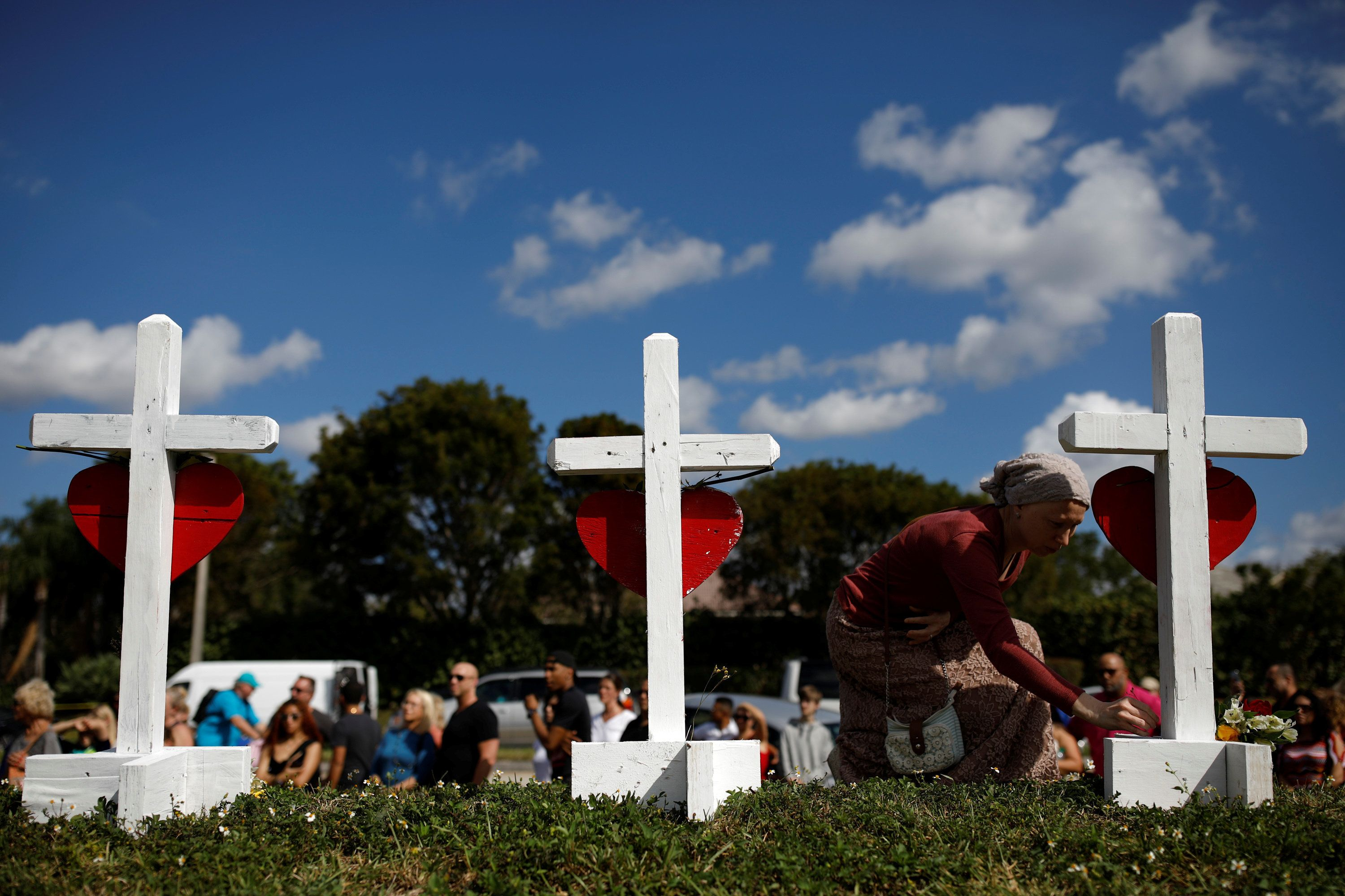 Elena Wright (L) mourns while she puts flowers at the crosses placed in front of the fence of the Marjory Stoneman Douglas High School to commemorate the victims of the mass shooting, in Parkland, Florida, U.S., February 18, 2018. REUTERS/Carlos Garcia Rawlins