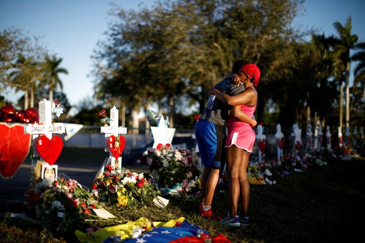 Marjory Stoneman Douglas High School student Adin Chistian, 16, embraces his mother, Denyse, at the memorial to victims of the Parkland shooting on Feb. 19, 2018.