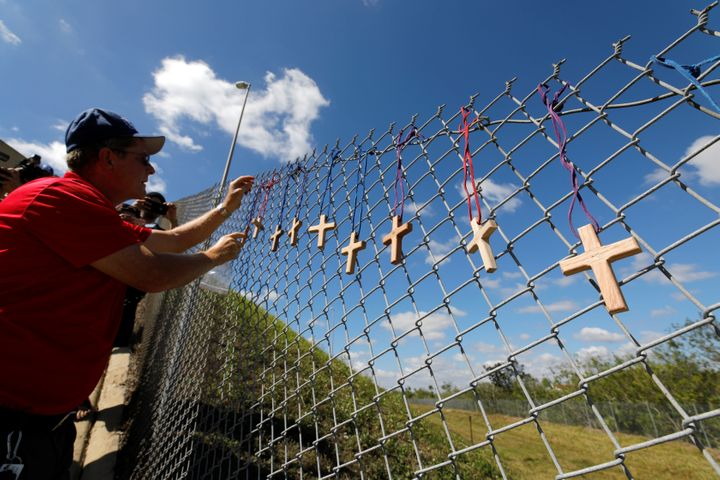 Bob Ossler, chaplain with the Cape Coral volunteer fire department, affixes 17 crosses on a fence for the victims of the