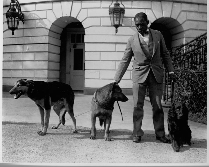 White House kennel master Robert R. Robinson stands with three of Hoover's dogs: (from left to right) Buckeye, King