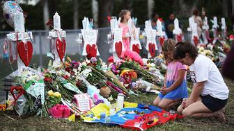 PARKLAND, FL - FEBRUARY 19:  People visit a makeshift memorial setup in front of Marjory Stoneman Douglas High School on February 19, 2018 in Parkland, Florida. Police arrested and charged 19 year old former student Nikolas Cruz for the February 14 shooting that killed 17 people.  (Photo by Joe Raedle/Getty Images)