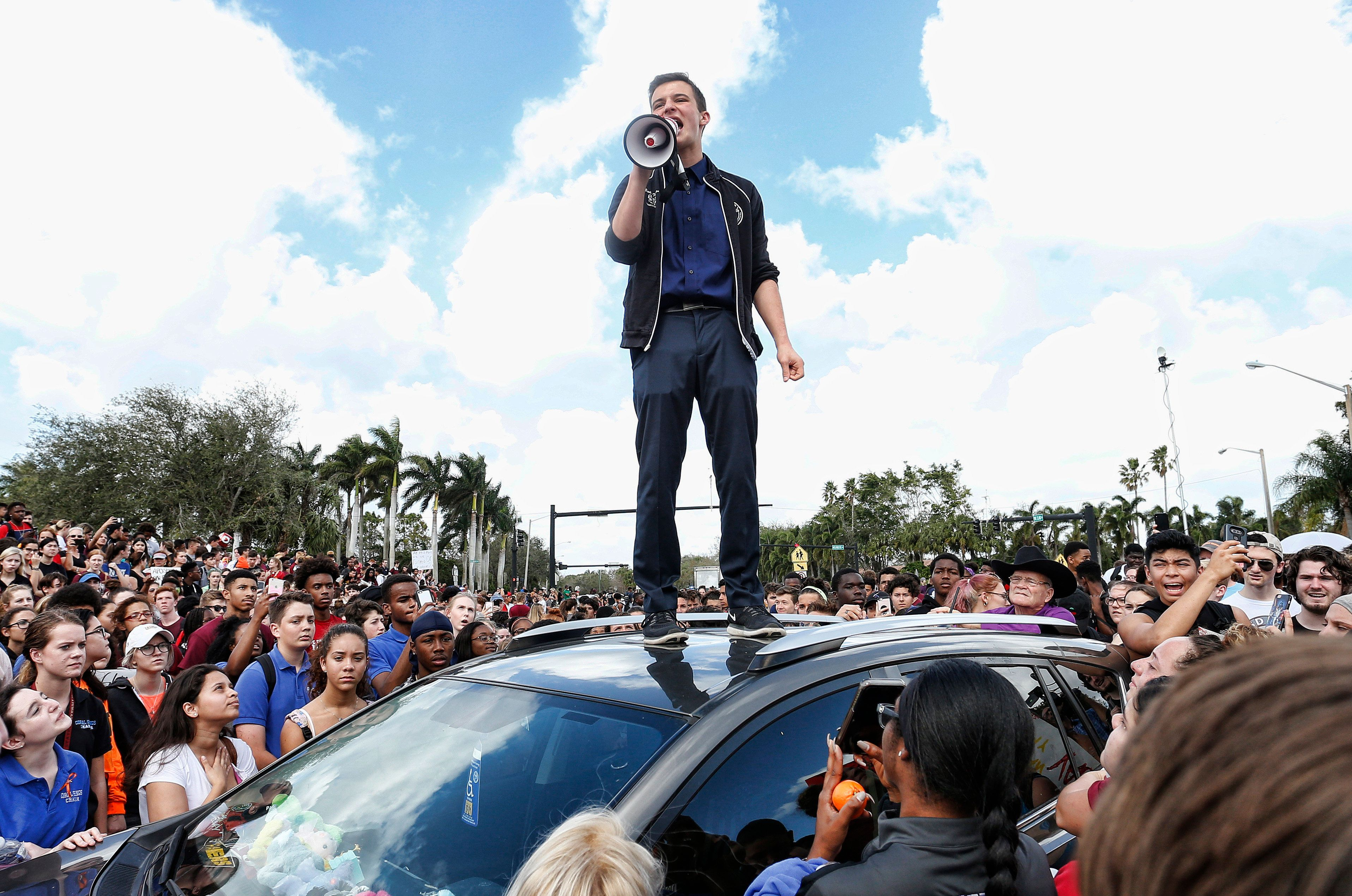 Majory Stoneman High School student Cameron Kasky addresses area High Schoolstudents as they rally at Marjory Stoneman Douglas High School after participating in a county wide school walk out in Parkland, Florida on February 21, 2018.  A former student, Nikolas Cruz, opened fire at Marjory Stoneman Douglas High School leaving 17 people dead and 15 injured on February 14. / AFP PHOTO / RHONA WISE        (Photo credit should read RHONA WISE/AFP/Getty Images)