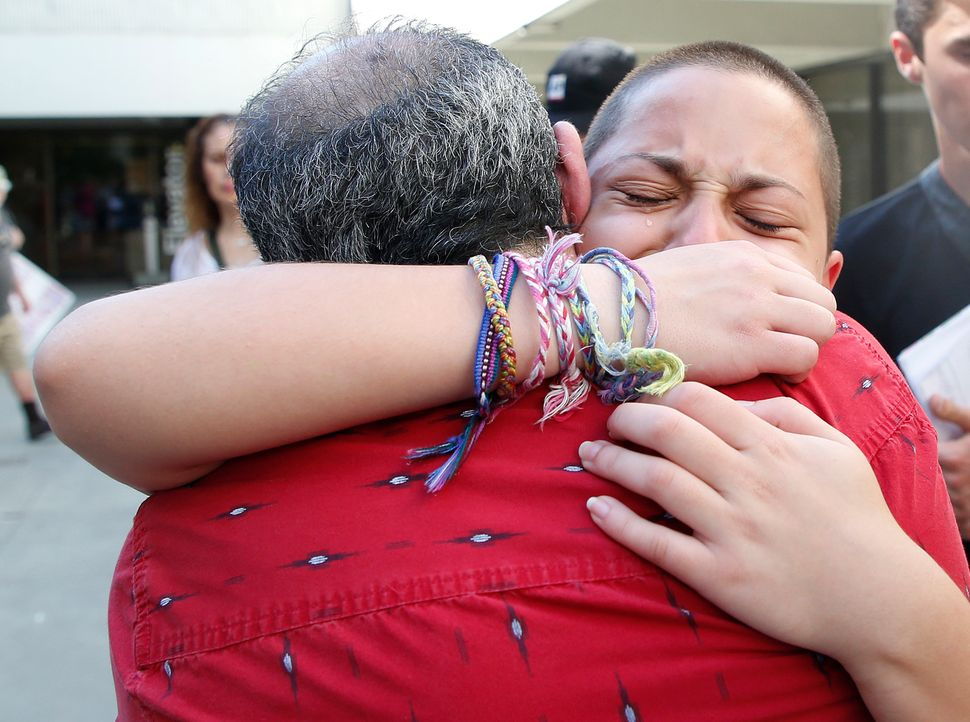 Marjory Stoneman Douglas High School student Emma González hugs her father Jose after speaking at a rally for gun cont