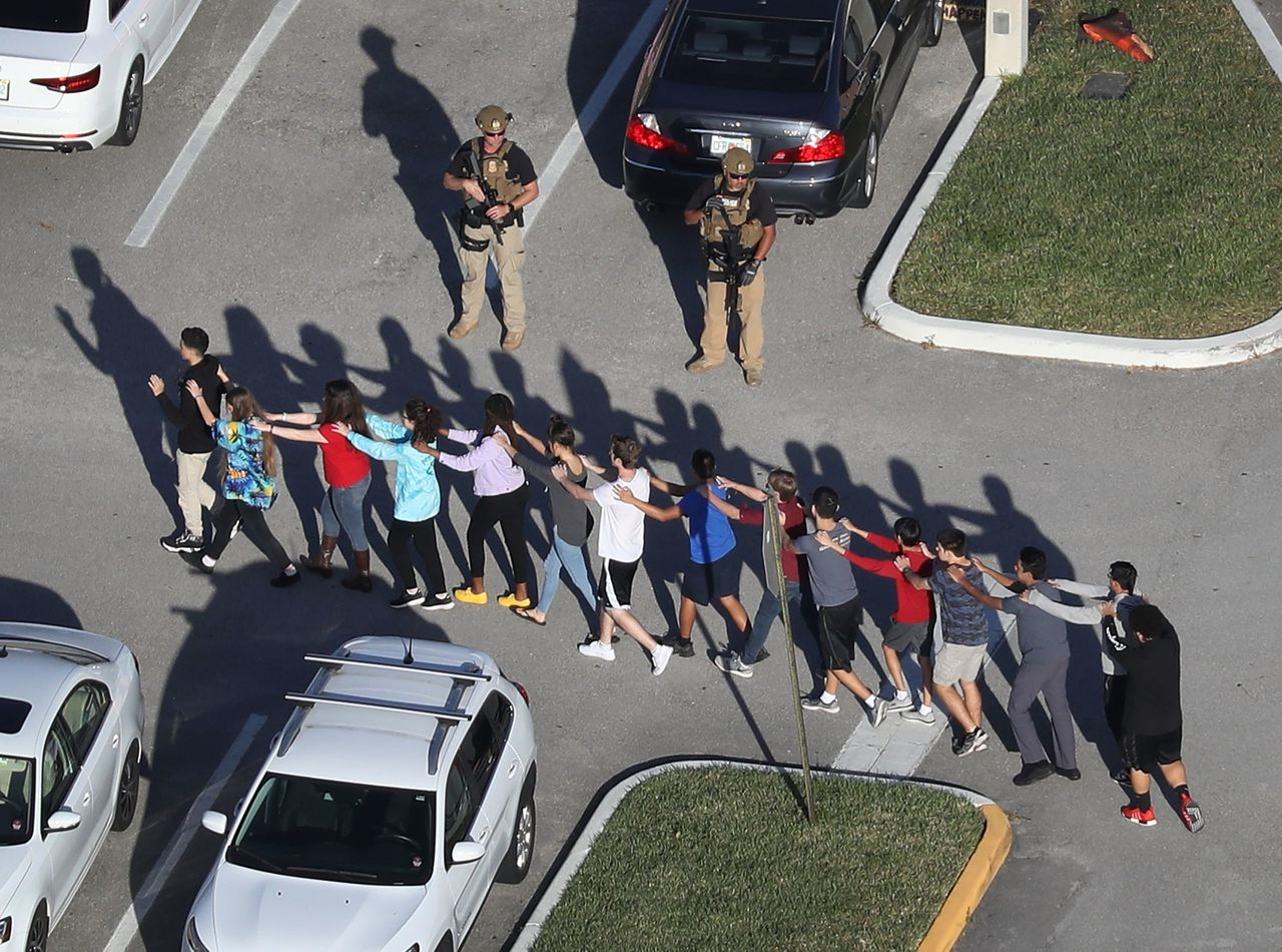 Students are escorted out of Marjory Stoneman Douglas High School after a shooting at the school in Parkland, Florida, last week.