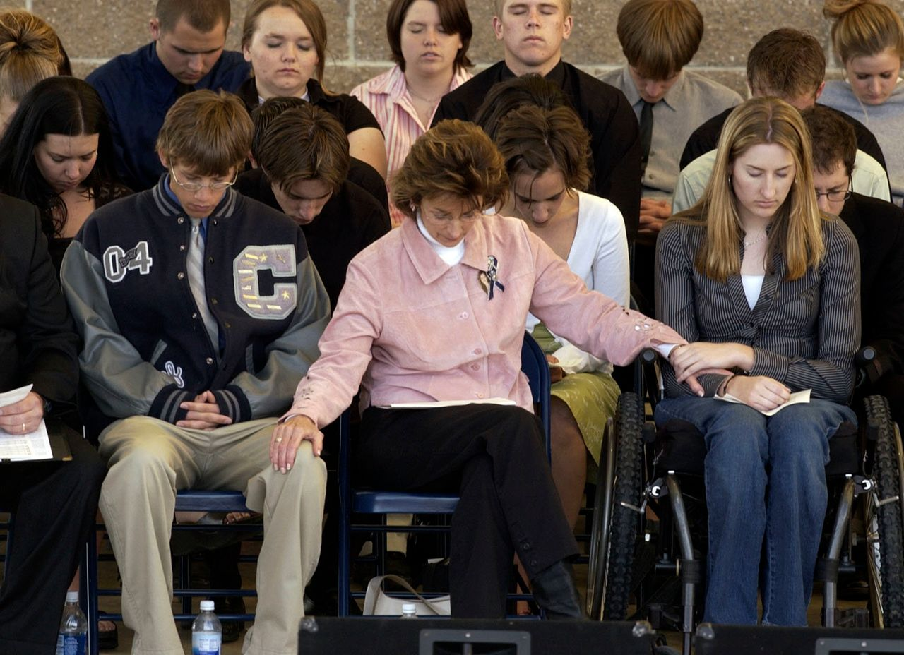 Anne Marie Hochhalter (right) prays during an event to remember those lost during the Columbine attack. She says she became disillusioned with her lawmakers over time.