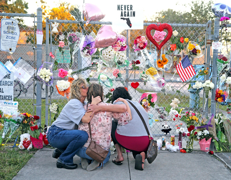Shari Unger kisses Melissa Goldsmith as Giulianna Cerbono lights candles at a memorial at Marjory Stoneman...