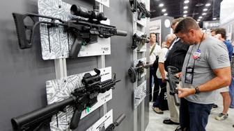 Gun enthusiasts look over Sig Sauers guns, including the Sig Sauer MCX rifle at top left, at the National Rifle Association's (NRA) annual meetings & exhibits show in Louisville, Kentucky, May 21, 2016.   REUTERS/John Sommers II