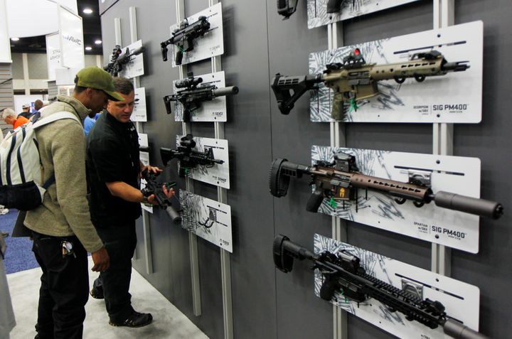 Gun enthusiasts view Sig Sauer rifles at the National Rifle Association's annual meetings and exhibits show in Louisville, Ke