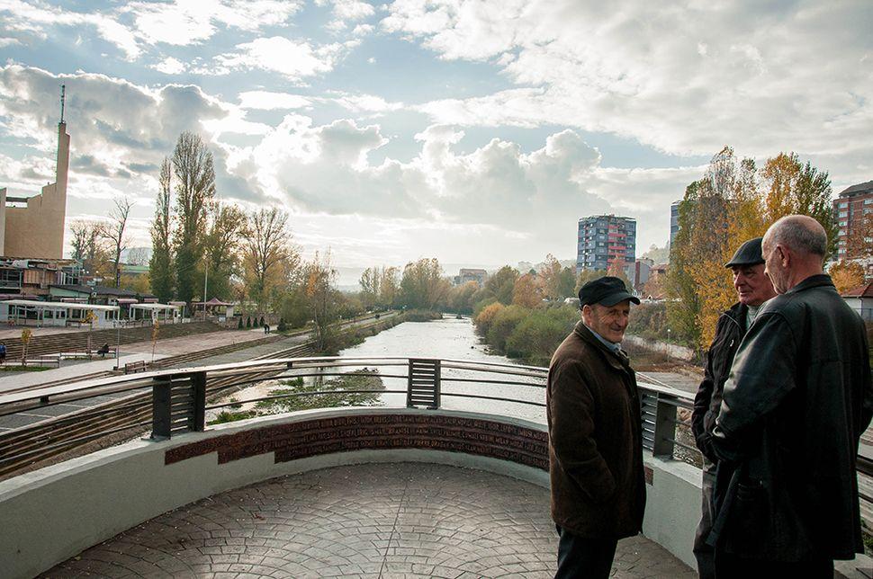 Λιγοστοί κάτοικοι τις Μιτρόβιτσα επιμένουν να συναντιούνται επάνω στη γέφυρα.