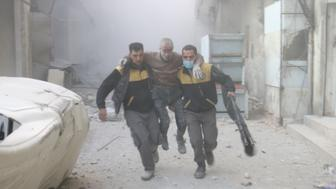 DAMASCUS, SYRIA - FEBRUARY 23: Civil defense members carry a wounded man after Assad regime forces carried out airstrikes over the de-escalation zone in Arbin town of Eastern Ghouta in Damascus, Syria on February 23, 2018. (Photo by Qusay Noor/Anadolu Agency/Getty Images)