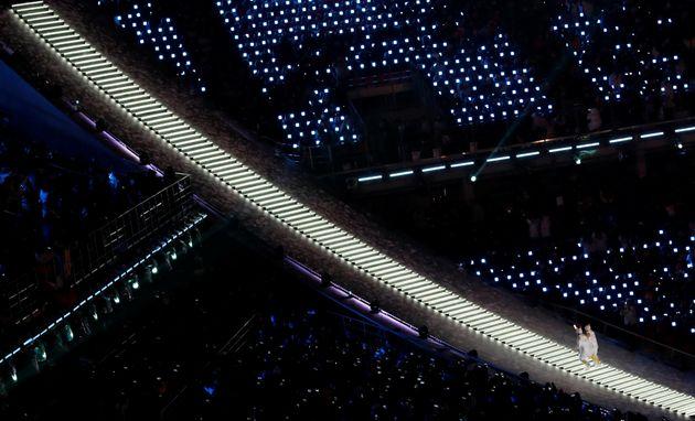 여자 아이스하키 남북단일팀 선수들이 성화를 들고 계단을 오르고 있다. 양옆으로 관객석에 밝은 조명들이