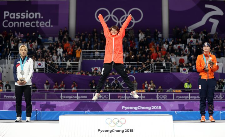 Nana Takagi celebrates her gold-medal mass speed skating win on the podium.