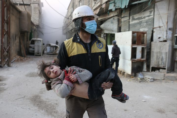 Civil defense team member carries a wounded baby rescued from a wreckage after Assad regime forces carried out airstrikes ove