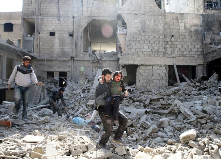 A man carries an injured boy as he walks on rubble of damaged buildings in the rebel held besieged town of Hamouriyeh, easter