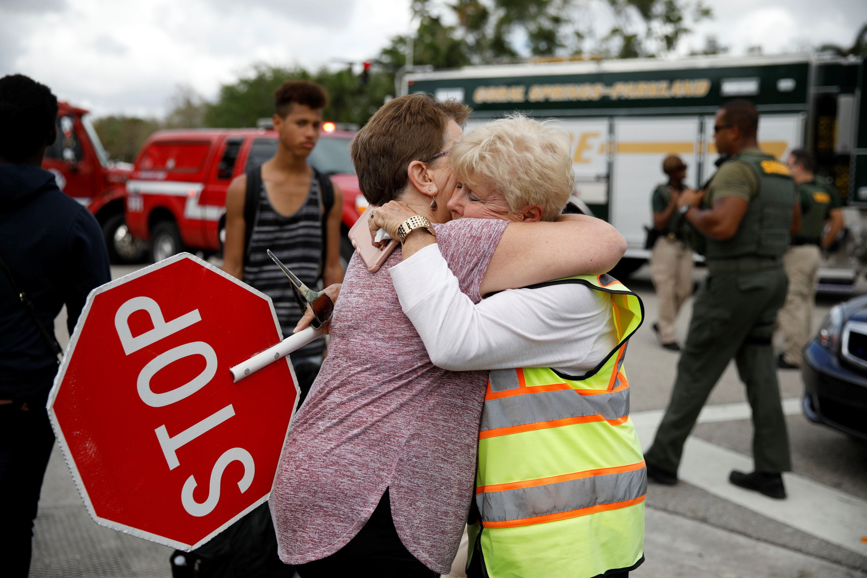 Crossing guard hugs student at Majory Douglas Stoneman High School in Parkland as kids return to classes after mass shooting