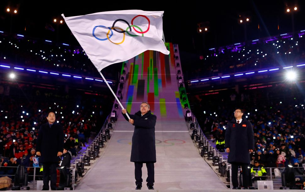 International Olympics Committee President Thomas Bach waves the Olympic flag.
