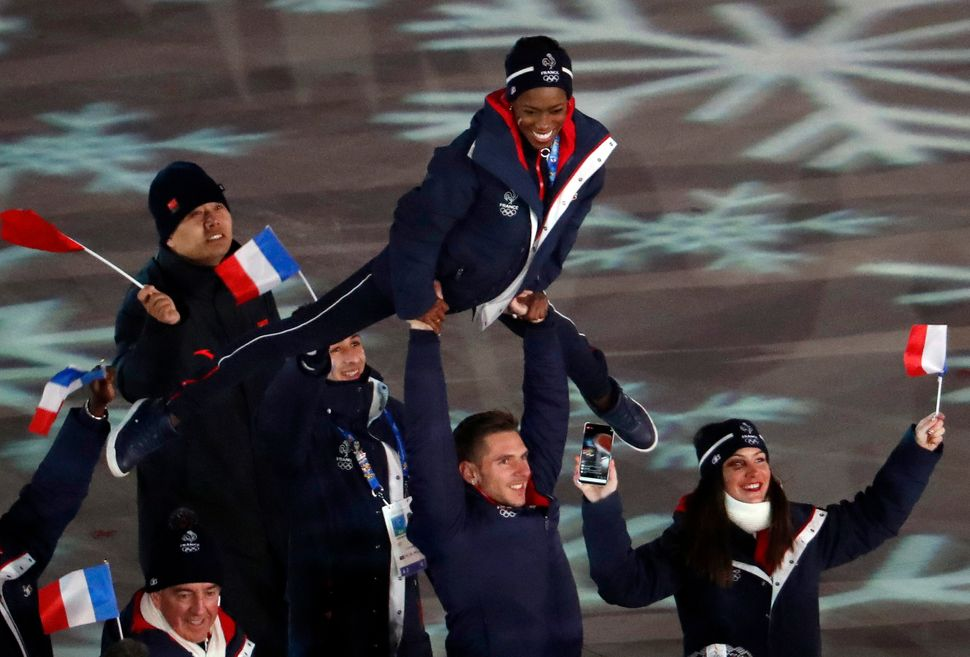 A French athlete is held in the airalongside France's flag.