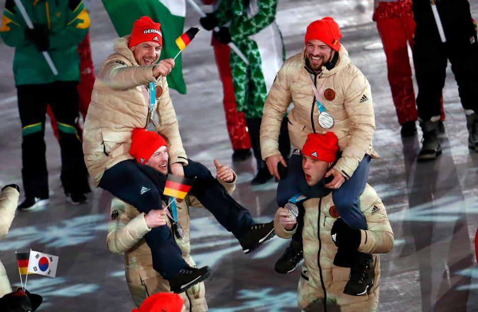 German silver ice hockey playerscelebrateduring the closing ceremony.