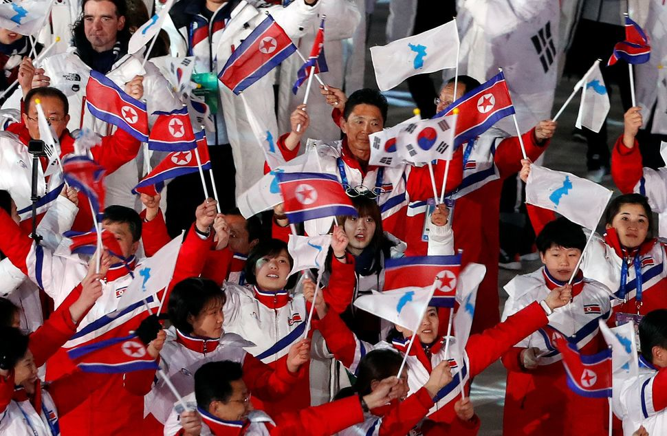 Athletes from North Korea and South Korea wave their flags.